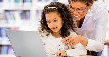 Teacher managing student's online behavior at laptop