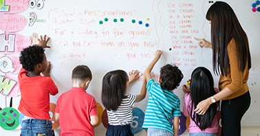 Primary students writing rhymes on a whiteboard with a teacher helping