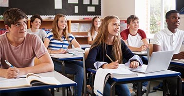 High School students sitting at their desks smiling towards the front of a classroom.