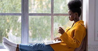Teacher sitting in a large windowsill while reviewing her laptop and having a warm drink