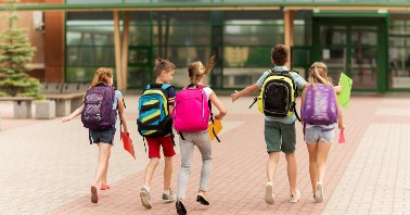 Middle School students returning to school walking with backpacks
