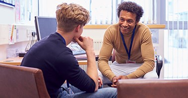 Teacher smiles while sitting and meeting with a high school student in a classroom setting.