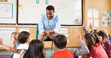 Middle school teacher smiles and points at a student sitting on the floor with other students, all with raised hands