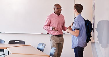 High school teacher and student stand in front of classroom whiteboards having a conversation
